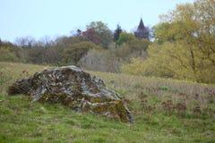 Unregelmäßiger Block nahe der Stadt von Hohendorf in Mecklenburg-Vorpommern Die Kirche der Stadt kann im Hintergrund gesehen werd Stockbild