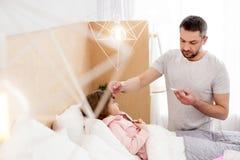 Unrested pappa som tar omsorg av hans sjuka dotter Royaltyfri Bild