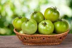 Unripe green tomatoes in a wicker basket on wooden table with blurred background Stock Photos