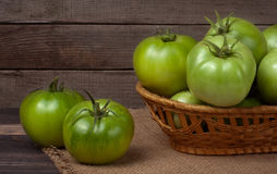 Unripe green tomatoes in a wicker basket on wooden table with sacking Stock Image