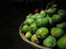 Unripe mangoes in market with perfect light stock images
