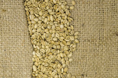 Unroasted coffee beans on hemp background Stock Photos