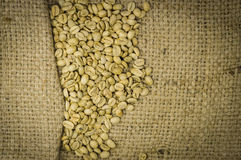 Unroasted coffee beans on hemp background Stock Image