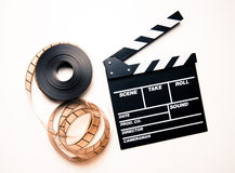 Unrolled 35mm movie reel and clapperboard in vintage color effec Stock Photos