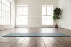 Unrolled yoga mat on wooden floor in yoga studio