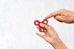 Unruhespinner Roter Handspinner, die Jungen, die mit der beunruhigenden Hand spielen, spielen Entspannung Antidruck und Entspannu Stockfotos