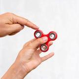 Unruhespinner Roter Handspinner, die Jungen, die mit der beunruhigenden Hand spielen, spielen Entspannung Antidruck und Entspannu Stockbild