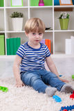 Unruly child. Sitting on floor with toys Royalty Free Stock Photos