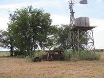 Uns comp(s) nortes velhos da exploração agrícola de Texas; ete com moinho de vento e o carro 1930 velho do ` s imagens de stock