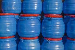 Uns grandes tambores plásticos azuis com tampões e os punhos vermelhos fotografia de stock