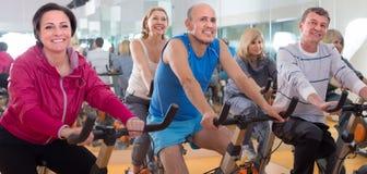 Uns homens mais idosos e as mulheres são contratados no gym Imagens de Stock Royalty Free