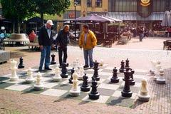 Uns homens mais idosos jogam no quadrado em Amsterdão com grande parte de xadrez fotografia de stock royalty free