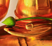 Uns lótus nas mãos da estátua de Buddha no templo dentro Fotos de Stock Royalty Free