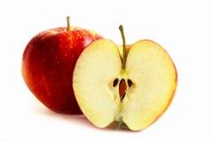 Uns maçã e um meio em uma tabela branca imagens de stock royalty free
