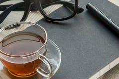 Uns pena, caderno, vidro e chá de vidro imagens de stock royalty free