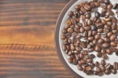 Uns pires com feijões de café estão em uma cama de madeira Imagens de Stock