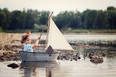 Uns pouco quatro anos do marinheiro idoso do menino no rio na pesca e na navigação do barco fotos de stock