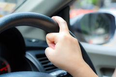 Unsafe hand on the steering wheel during on driving.  Royalty Free Stock Image