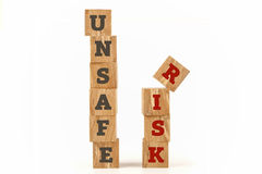 Unsafe and Risk word written on cube shape. Unsafe and Risk word written on cube shape wooden surface isolated on white background Stock Photography