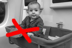 Unsafety and danger flight concept, Read the rules. Baby in special bassinet seat in airplane.  stock images