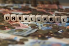 Unsaleable - cube with letters, money sector terms - sign with wooden cubes Stock Images