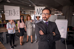 Unsatisfied employees on strike in the office. Unsatisfied employees on strike in the office, director standing with his back to employees. Modern office stock image