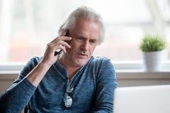 Unsatisfied hög man som talar på mobiltelefonen arkivbild