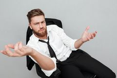 Unsatisfied tired businessman sitting in a chair. And gesturing with hands isolated over gray background Royalty Free Stock Image