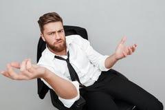 Unsatisfied trött affärsmansammanträde i en stol royaltyfri bild