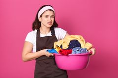 Unsatisfied upset housewife standing with unpleasant facial expression, holding pink basin full of dirty clothes, wearing light royalty free stock images