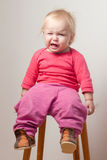 Unsatisfied Young Baby Sit On Chair Royalty Free Stock Images