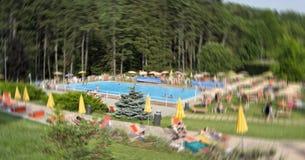 Unschärfebild des Swimmingpools der Leute öffentlich im Wald während der Sommersaison Lizenzfreie Stockfotografie