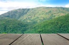 Unschärfebild des Terrassenholzes und des schönen grünen Berges Stockbild