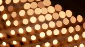 Unschärfekirche leuchtet Lichter durch Kleine Kerzen auf Tabelle in der katholischen Kirche