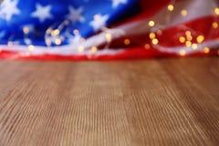 Unscharfe amerikanische Flagge und Girlande auf Holztisch lizenzfreies stockbild