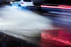 Unscharfe Ansicht des Wassers spritzt von den Autorädern während des regnerischen weat Stockfotografie