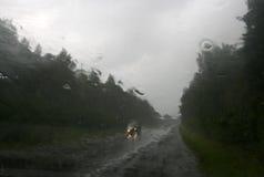 Unscharfe Ansicht: die Straße, der Wald und das Auto im Gießen regnen Lizenzfreie Stockfotografie