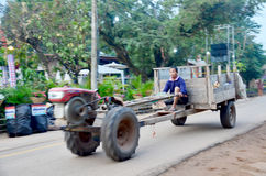 Unscharfe Bewegung des Mannes des thailändischen ethnischen Fahrtraktors Phu und traile Stockbild