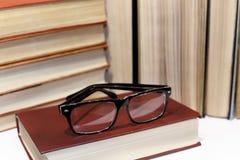 Unscharfe Gläser und Stapel der Buchnahaufnahme lizenzfreie stockfotografie