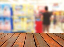 Unscharfe hölzerne Tabelle des Bildes auf bokeh Licht des Kaufhauses in s Stockbilder