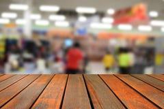 Unscharfe hölzerne Tabelle des Bildes und abstrakte Rückseite des Supermarktspeichers an Lizenzfreies Stockfoto