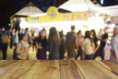 Unscharfe hölzerne Tabelle und Lebensmittel des Bildes am Nachtfestival mit bokeh b Lizenzfreie Stockfotografie