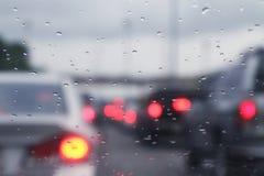 Unscharfe Hintergrundverkehrsautostau- und -regentropfen wässern auf Glas mit bokeh Beleuchtungsauto stockfotografie