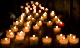 Unscharfe Kerzen brennen in einer Kirche Lizenzfreies Stockfoto