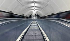Unscharfe Leute auf Rolltreppe an der Hauptverkehrszeit. Lizenzfreies Stockfoto