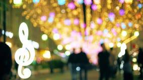 Unscharfe Leute gehen entlang belichtete Fußgängerstraße am Abend stock footage