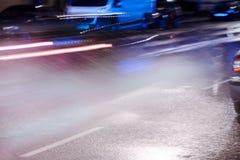 Unscharfe rote Scheinwerfer des Autofahrens auf überschwemmtes Nachtstraße duri Stockfotografie