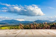 Unscharfe und hölzerne Tabelle der Zusammenfassung, schöne Berge gestalten landschaftlich Lizenzfreie Stockfotos
