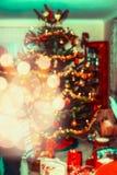 Unscharfe Weihnachtsausgangsszene mit verziertem Weihnachtsbaum, Geschenken und festlichem bokeh Stockbilder