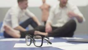 Unscharfe Zahlen von zwei Männern in den weißen Hemden, die auf dem Boden im Hintergrund sitzen Papiere und Gläser auf dem Boden  stock video